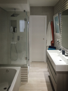 Renovated bathroom with double sink, bath and shower