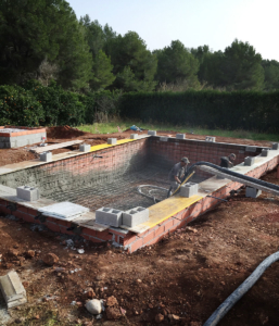 Workers putting in heavy coating of gunite around the rebar for the new pool.